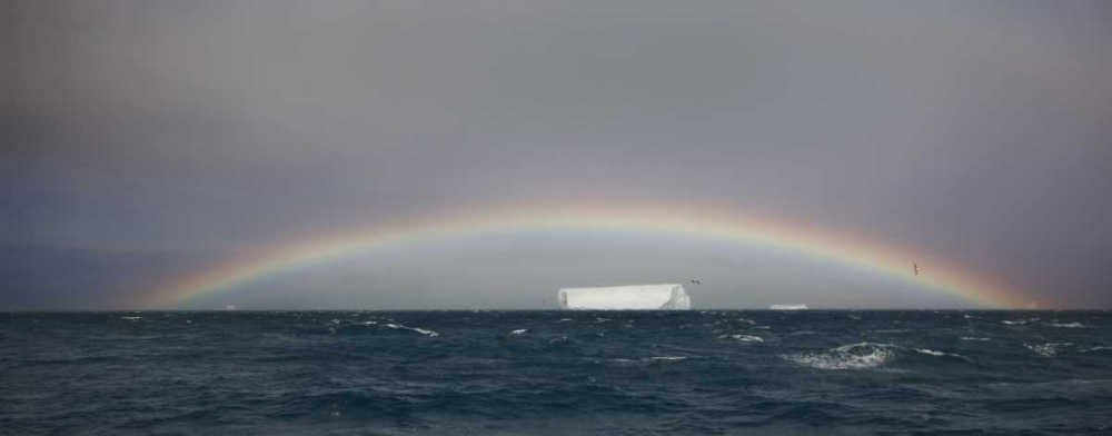 Antarctica, A tabular iceberg under a low rainbow poster print by Don Grall